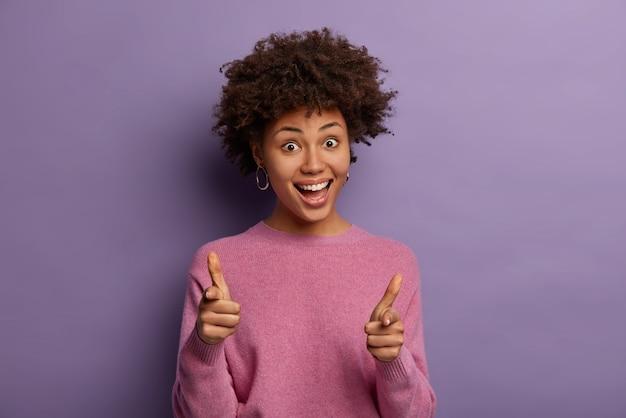 La donna afroamericana felice e divertente con l'acconciatura riccia punta le pistole del dito alla macchina fotografica, finge di sparare, sceglie o ti prende, dice bang bang