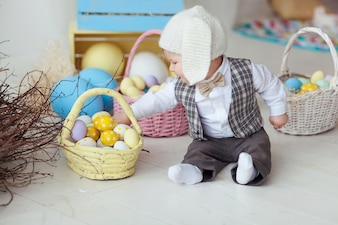 Funny happy baby boy in hat, tie bow and suit playing with Easter eggs.