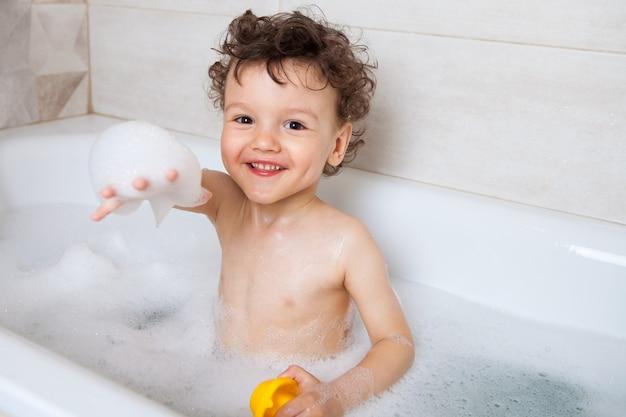 おかしい幸せな赤ちゃん、男の子は水と泡で浴槽を浴びます。泡で手を前に引きます。病気の予防としての衛生手順