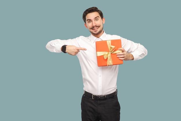 Забавный счастливый бородатый мужчина в белой рубашке, стоящий и держащий красную подарочную коробку, указывая пальцем в настоящее время и смотрящий в камеру с зубастой улыбкой. крытый, студийный снимок, изолированные на светло-синем фоне