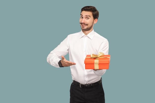 Забавный счастливый бородатый мужчина в белой рубашке, стоящий и держащий красную подарочную коробку, показывая и смотрящий на камеру с зубастой улыбкой. крытый, студийный снимок, изолированные на светло-синем фоне