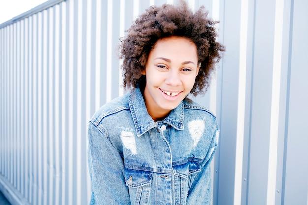 Смешная счастливая черная афро женщина в белой футболке и джинсах