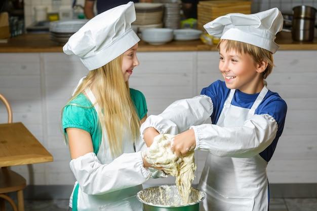 面白い幸せな男の子と女の子のレストランで料理