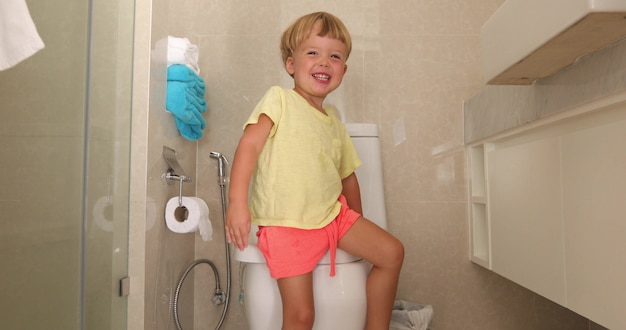 Funny happy child sitting on toilet and looking at camera in lavatory