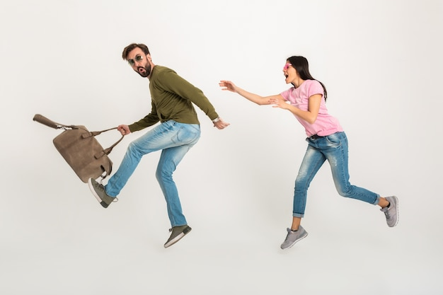 Funny happy couple jumping isolated, pretty smiling woman in pink t-shirt running after man in sweatshirt holding travel bag, dressed in jeans