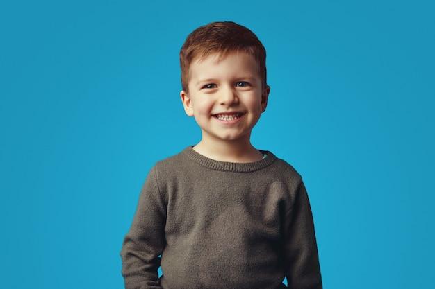Забавный счастливый милый ребенок мальчик в повседневной рубашке выглядит очень взволнованным, улыбаясь Premium Фотографии