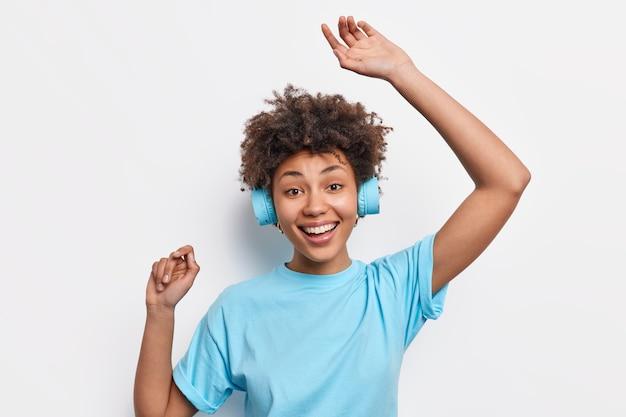 音楽のリズムで踊るカジュアルなベーシックなtシャツを着た面白い幸せな暗い肌の若いアフリカ系アメリカ人女性は、白い壁に隔離されたステレオヘッドフォンを着用しています。人々はライフスタイルの趣味の概念を喜ぶ