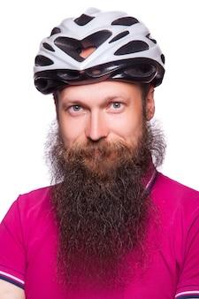 분홍색 또는 보라색 티셔츠가 달린 헬멧을 쓴 재미있는 유럽의 수염 난 자전거. 사람들에게 보호를 조언합니다. 스튜디오 촬영. 흰색에 격리.