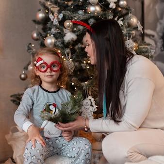 Смешная счастливая семья, мама и маленькая дочь в модных пижамах сидят возле елки с огнями. зимние каникулы дома