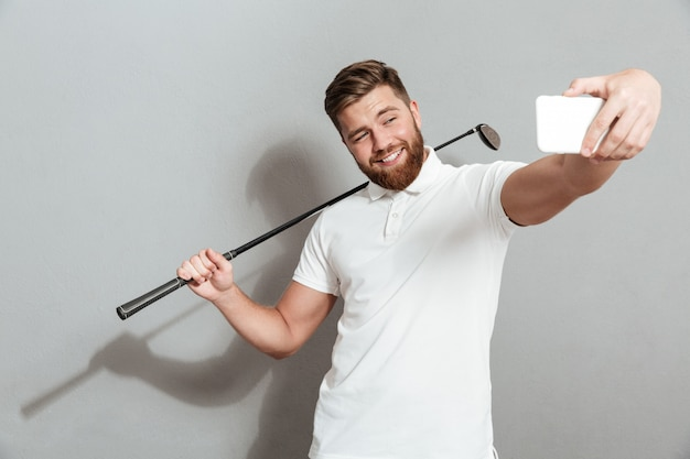 Funny happy golfer making selfie on his smartphone