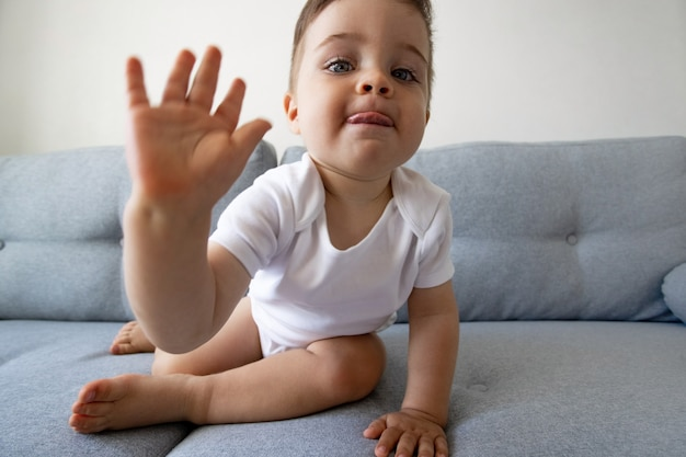 Funny happy healthy toddler one year old sitting at the sofa at home pretty eyes kids play and child...