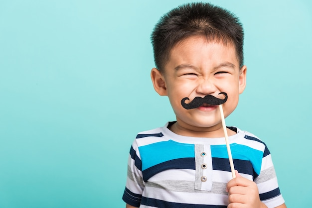 フォトブースの近くの顔のための黒い口ひげの小道具を保持している面白い幸せな流行に敏感な子供