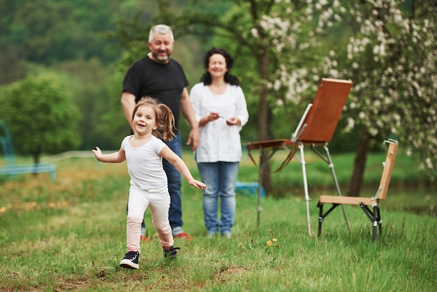 面白い幸せな子供。祖母と祖父は孫娘と屋外で楽しんでいます。絵画の構想