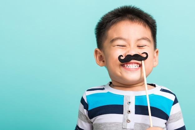 フォトブースの近くの顔のために黒い口ひげの小道具を持っている面白い幸せな子供