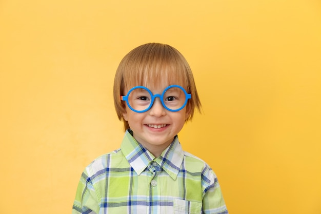Funny happy little boy in glasses and shirt smiling