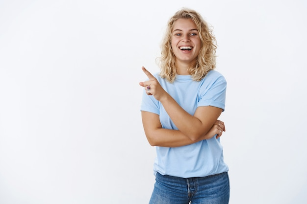 Donna europea ottimista divertente e felice degli anni '20 con capelli biondi ricci corti e occhi azzurri che sorride sinceramente e felicemente mentre indica l'angolo in alto a sinistra al prodotto che le piace, sorride ampiamente alla telecamera