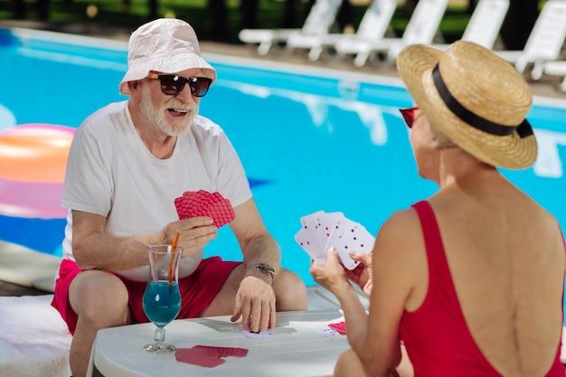 Забавные счастливые пенсионеры в яркой одежде, развлекательные, сидя возле большого открытого бассейна