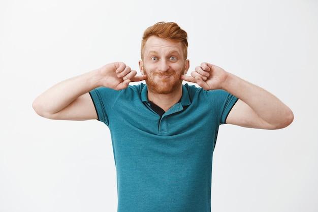 Uomo dai capelli rossi divertente e felice, gonfio, trattenendo il respiro e colpendo le guance mentre sorride ampiamente, scherzando e facendo smorfie sul muro grigio