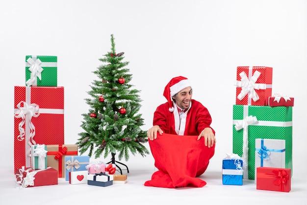 贈り物と白い背景の上の地面に座って飾られたクリスマスツリーでサンタクロースに扮した面白い幸せな若い大人
