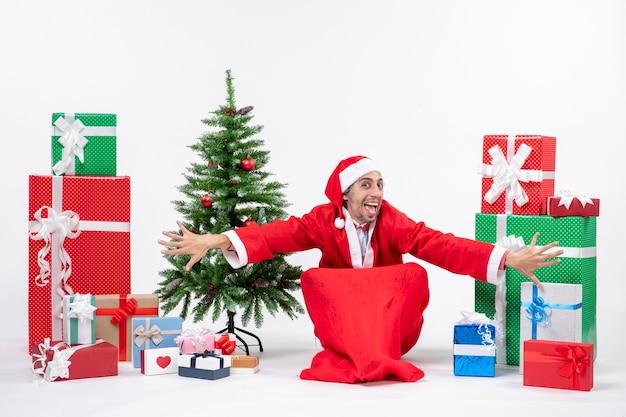 Забавный счастливый молодой человек в костюме санта-клауса с подарками и украшенной елкой сидит на земле на белом фоне