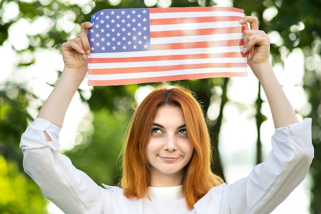 Funny happy young woman posing with usa national flag up over her head standing outdoors in summer park. positive girl celebrating united states independence day.