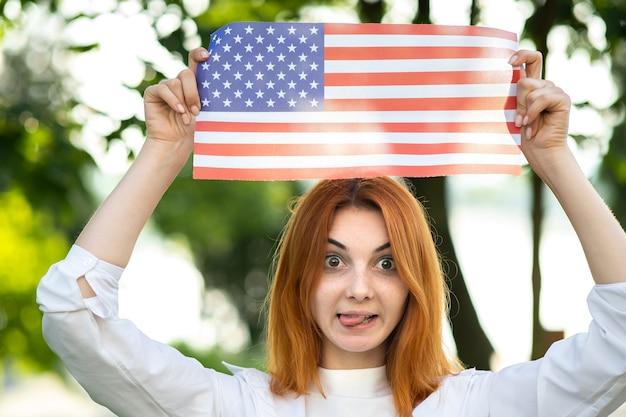 여름 공원에서 야외 서 그녀의 머리 위로 미국 국기와 함께 포즈를 취하는 재미 행복 한 젊은 여자