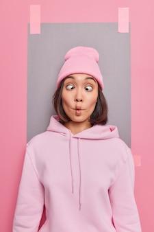 웃긴 힙스터 소녀는 카메라를 보고 물고기 입술이 눈을 찡그리게 하고 분홍색 모자를 쓰고 운동복 셔츠를 입고 실내 석고 광고판을 포즈를 취하여 광고를 바보인 척합니다