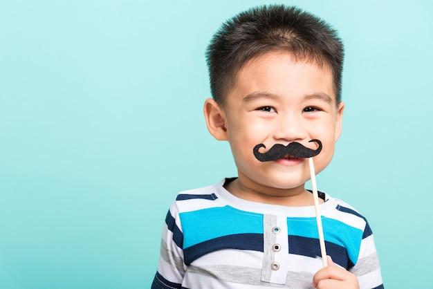 フォトブースのクローズフェイスの黒い口ひげの小道具を保持している面白い流行に敏感な子供