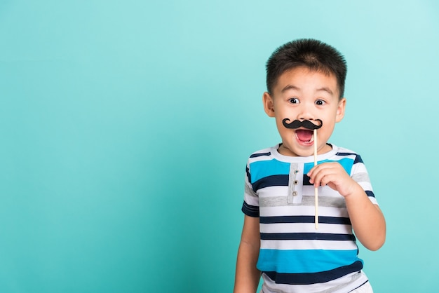 Funny hipster kid holding black mustache props for the photo booth close face