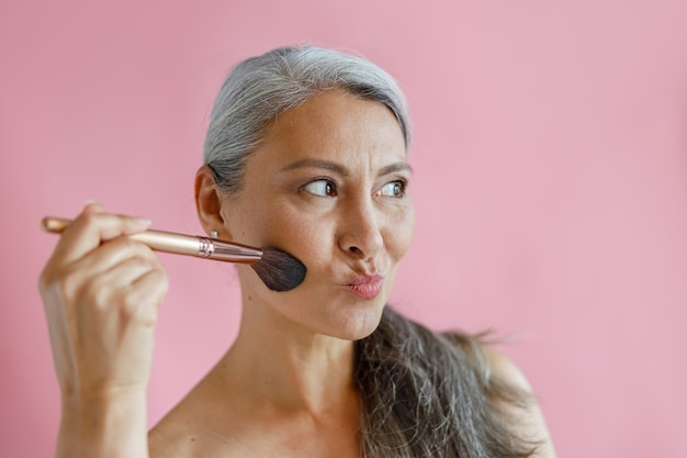 面白い白髪のアジアの女性はピンクの背景に顔をゆがめたブラシで化粧を適用します