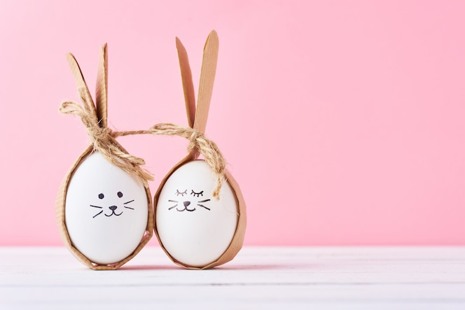 Funny homemade eggs with faces on a pink background. easter or happy couple concept