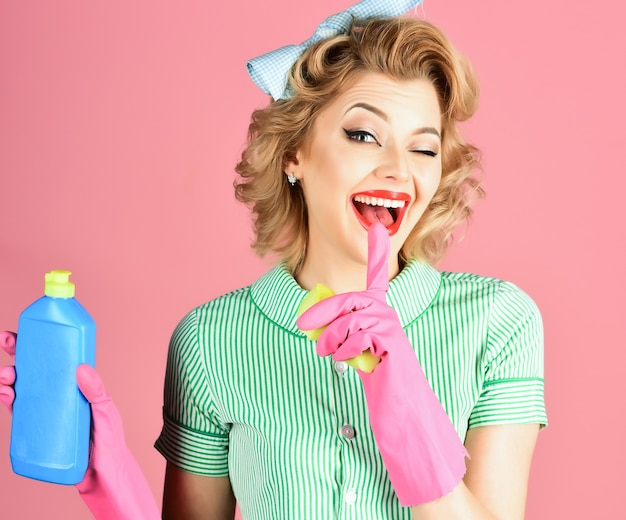 Funny housewife with cleaning sprayer housewife isolated woman housekeeper in uniform with clean spray sponge cleaning retro style purity housewife hold soup bottle sponge