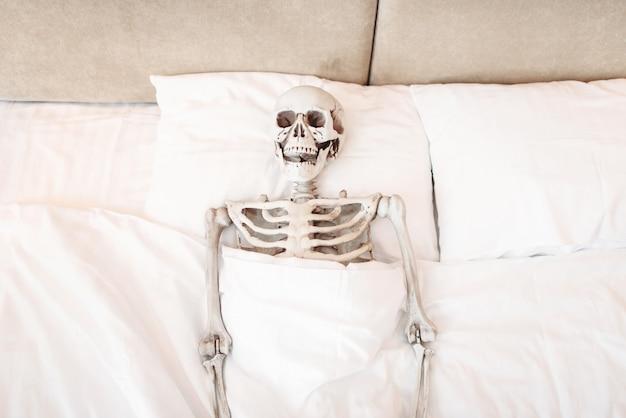 Funny human skeleton is lying in bad, top view. humor or joke concept