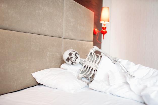 Funny human skeleton is lying in bad
