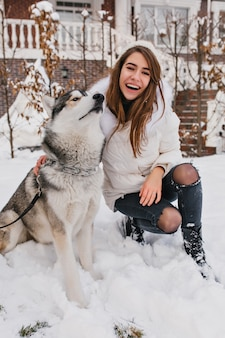 Funny husky resting after game in snowy park. outdoor portrait of elegant white woman in ripped jeans sitting on the ground near her beautiful dog in winter weekend.