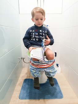 Funny image of little 3 years old toddler boy sitting on the toilet and reading magazine