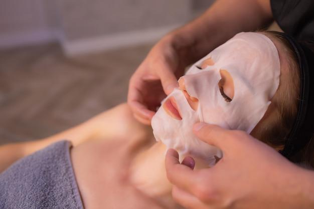 カメラ、化粧品の手順、スキンケアを見ている顔のマスクを持つ若者の面白い画像。