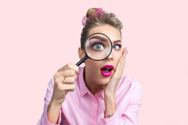 Funny image of young surprised female looking at the camera through a magnifying glass