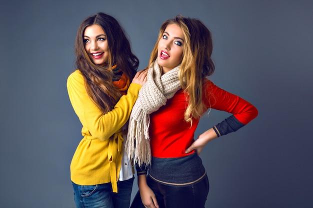 Забавный портрет девушки-хипстера, развлекающейся в студии в классических кашемировых свитерах и шарфах