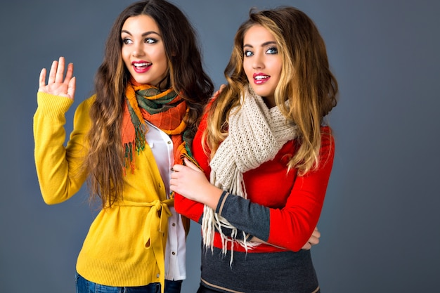 Funny indoor portrait of who hipster girls having fun in studio, wearing classic cashmere sweaters and scarfs