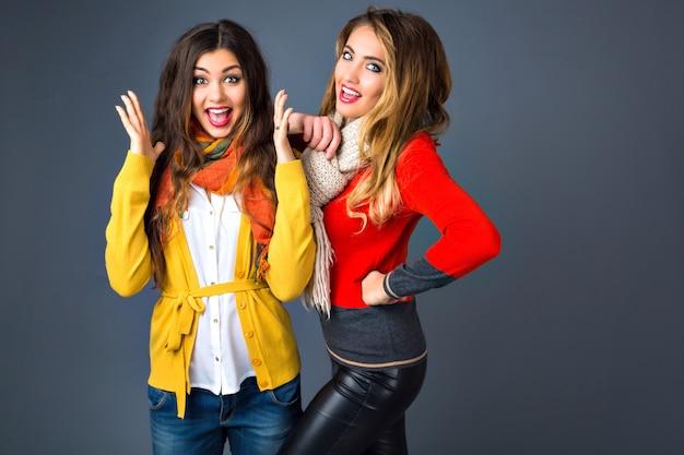 Divertente ritratto al coperto di ragazze hipster che si divertono in studio, indossando maglioni e sciarpe classici in cashmere