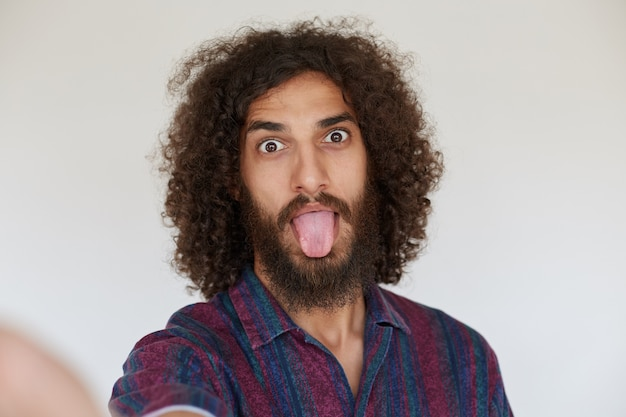 Colpo divertente dell'interno di giovane uomo barbuto riccio dai capelli scuri attraente che scherza e che fa le facce, vestito con la camicia multicolore a strisce