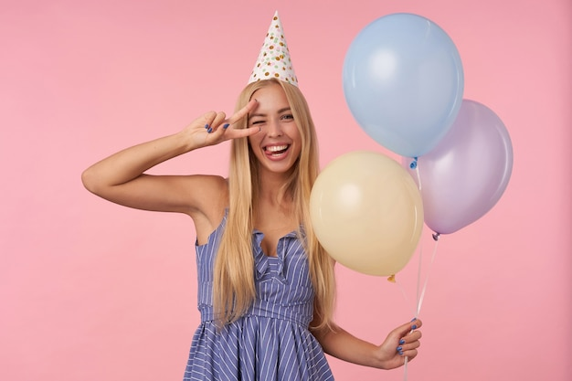 Funny indoor shot of young blonde woman with long hair giving wink and raising ok gesture happily, holding multicolored air balloons in her hands while posing over pink background