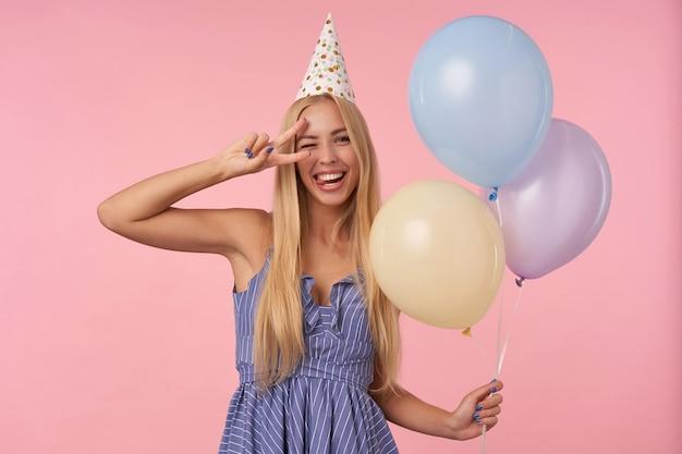 Colpo divertente dell'interno di giovane donna bionda con capelli lunghi che fa l'occhiolino e che alza felicemente il gesto giusto, che tiene gli aerostati multicolori nelle sue mani mentre posa sopra fondo rosa