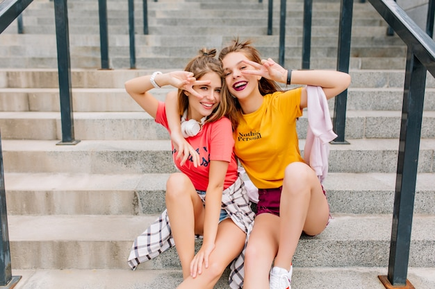 Funny inspired young ladies in trendy outfit gladly posing with peace sign relaxing on stone steps in summer day