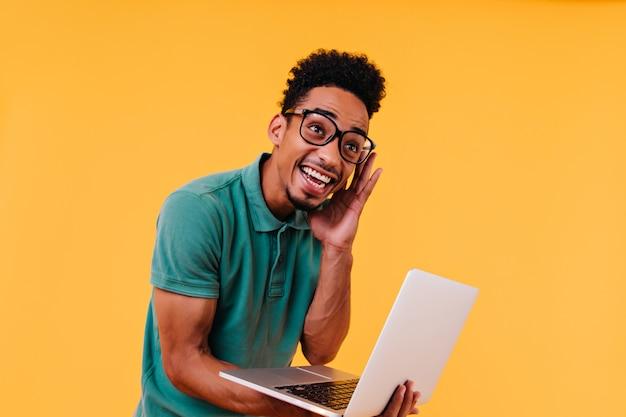 彼の仕事をしている面白い留学生。ラップトップを保持しているメガネで楽しい男性フリーランサーの屋内写真。