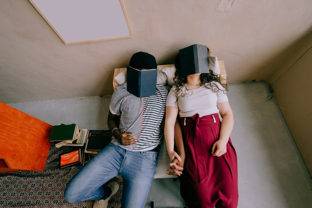 Funny interracial couple sitting in chair and sleeping with books on their faces.