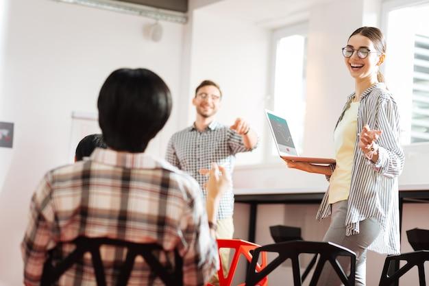 재미있는 농담. 현대 노트북과 함께 서서 동료와 함께 웃고 쾌활한 친절한 젊은 전문가