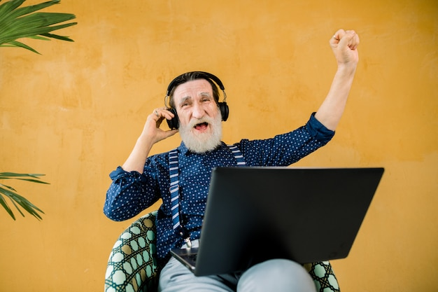 Funny joyful bearded man with earphones sitting in the chair on yellow wall background and using laptop computer