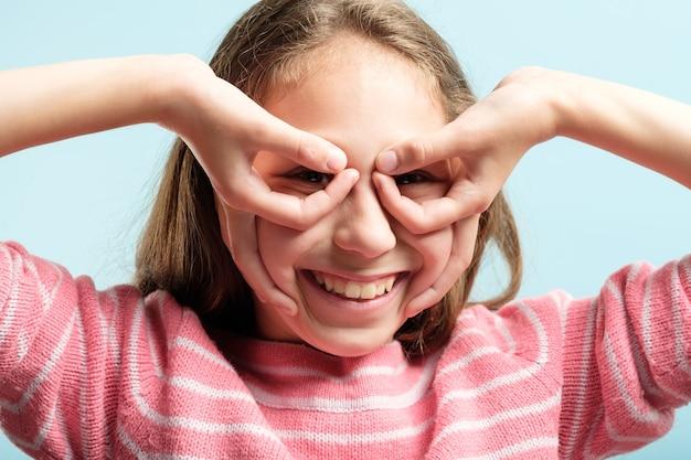 Забавная веселая комическая игривая девочка, притворяющаяся, что смотрит в бинокль из рук. эмоциональное выражение лица.